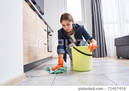 Woman carefully wiping the floor 71407458