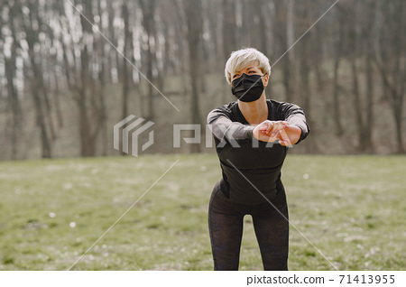 Masked woman training during coronavirus 71413955