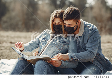 People in a masks sitting in a spring forest 71414233