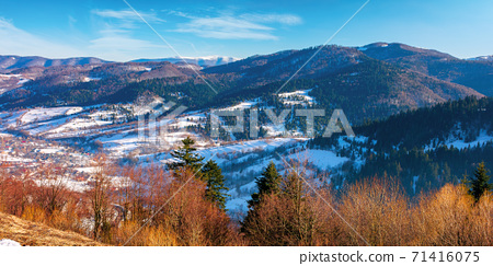 mountainous countryside on a sunny day. late winter scenery or beginning of spring. melting snow and leafless trees on the hills. village in the distant valley. transcarpathia, ukraine 71416075