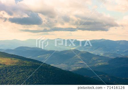 wonderful alpine landscape on summer evening. rolling hills of great mountain range in warm light beneath a fluffy clouds on a blue sky 71416126