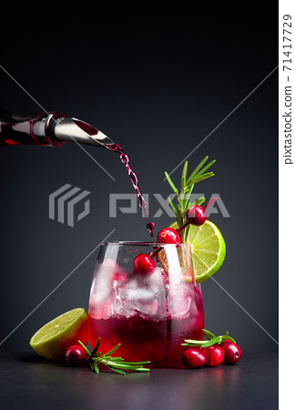 Cranberry cocktail garnished with berries, lime, and rosemary. 71417729