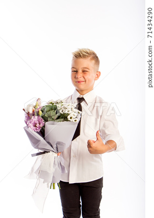 Cheerful blond fashionable boy gives bouquet and thumbs up on white studio background, delivery flowers, Spring Womens Day 71434290