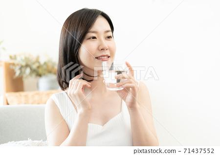 在客廳裡的中年女人喝水 71437552
