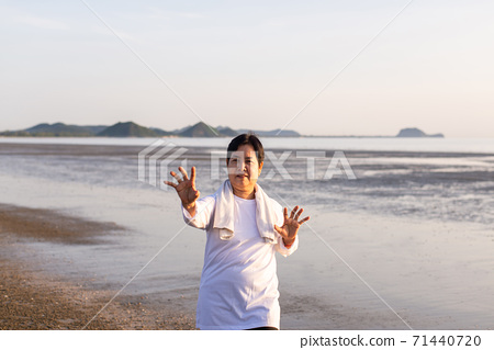Senior asian woman practicing Tai Chi exercise during sunset at the beach 71440720