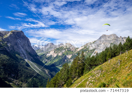 Paragliding over the pralognan mountains in the Vanoise National Park 71447319