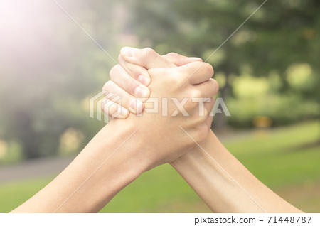 Two hands of teenagers are fighting among themselves in the park and the forest in the sport of armwrestling. The concept of rivalry and violence between teens in the education system 71448787