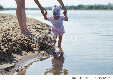 Mother and child walking on a sandy beach 71454217