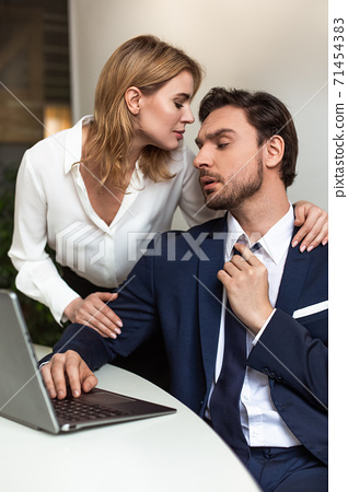 Passionate couple flirts in the office. Businessman looks on woman touching him from back while standing near workplace. Seducing concept 71454383