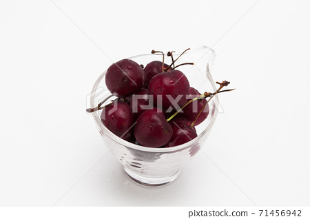 Sweet ripe cherry in glass cup isolated on whte background 71456942