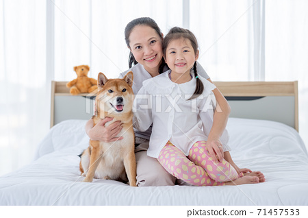 Asian mother and girl sit on white bed with Shiba dog and look to camera with smiling in bedroom 71457533
