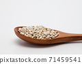 Wooden spoon with unhulled barley on white 71459541