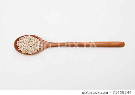 Wooden spoon with unhulled barley on white 71459544