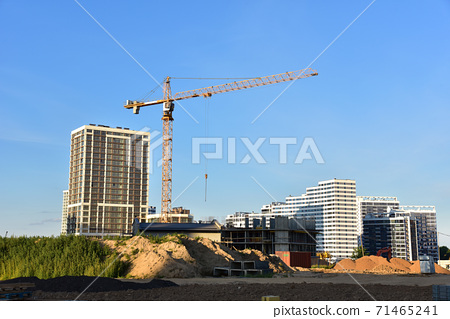 Tower crane working at construction site on blue sky background.  71465241