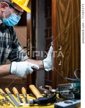 Carpenter at work protects the face with the surgical mask. Covid-19 prevention. 71465375