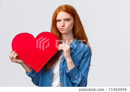 Serious-looking troubled, unsure cute redhead girl thinking what gift buy in addition to valentines day big red heart card, plan romantic date, pouting and frowning camera perplexed 71468999