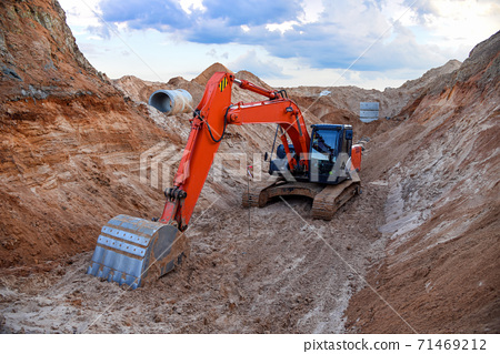 Excavator working at a construction site during laying or replacement of underground storm pipes 71469212