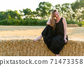 Woman in black long dress looking in camera standing in the field 71473358