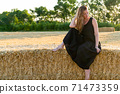 Woman in black long dress looking in camera standing in the field 71473359