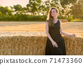 Woman in black long dress looking in camera standing in the field 71473360