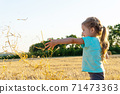 Little girl playing with wheat grass in the field 71473363