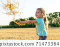 Little girl playing with wheat grass in the field 71473364