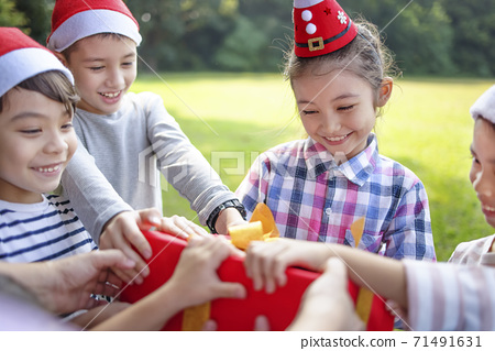 Happy children in Santa red hat and holding Christmas presents 71491631