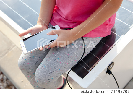 Child girl charges mobile phone via USB outdoors. Kid is sitting on bench with solar panel. Public charging on street 71495707