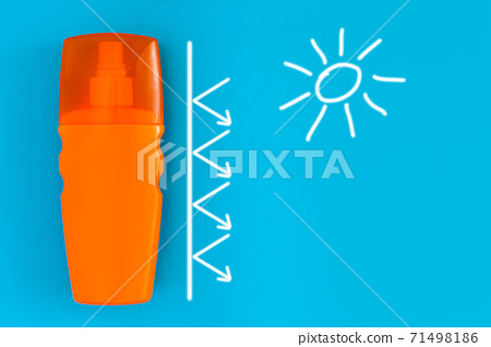 sunscreen in an orange plastic bottle with a spray on a blue background with white painted sun and a barrier with arrows, a conceptual photo of skin care, nobody. 71498186