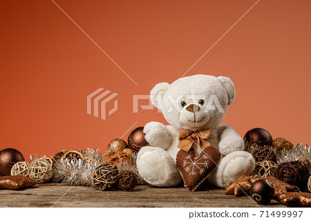 White or light brown adorable teddy bear with christmas decorations and gifts. Holiday concept with toy plush bear and christmass gifts on the wood table. 71499997