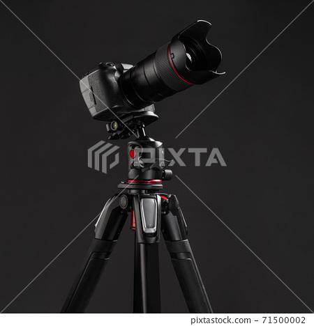 Professional photography equipment, digital mirrorless camera on tripod with dark gray background 71500002