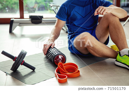 Various types of exercise equipment on the floor next to the young man 71501170