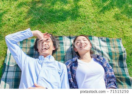 躺下在草坪的一對年輕夫婦 71515250