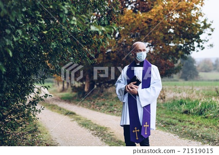 Catholic priest with a bible in a medical mask stands in a field in the countryside 71519015