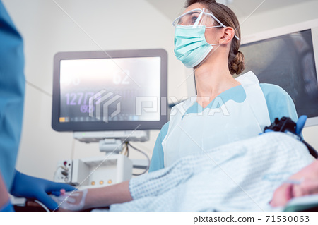 Doctor during colonoscopy in hospital looking at screen 71530063