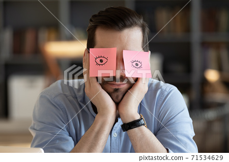 Employee hides eyes with sticky notes wants sleep at workplace 71534629