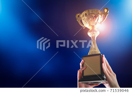 Business hands holding trophy cup on blue background. Selective focus 71539046