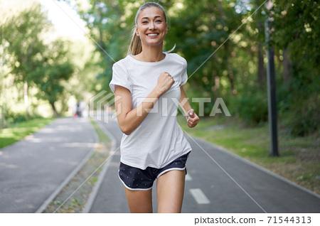 Woman running asphalt road summer park 71544313