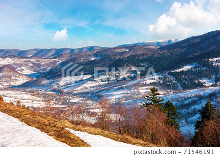 mountainous countryside on a sunny day. late winter scenery or beginning of spring. melting snow and leafless trees on the hills. village in the distant valley. transcarpathia, ukraine 71546191