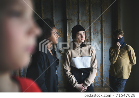 Group of teenagers gang standing indoors in abandoned building, bullying concept. 71547029