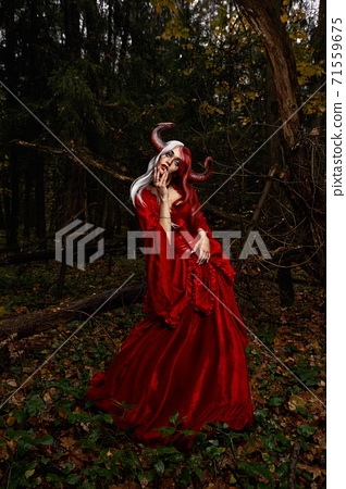 Maleficent Woman in Red Clothing and Horns in dark Forest. Posing in magik forest 71559675