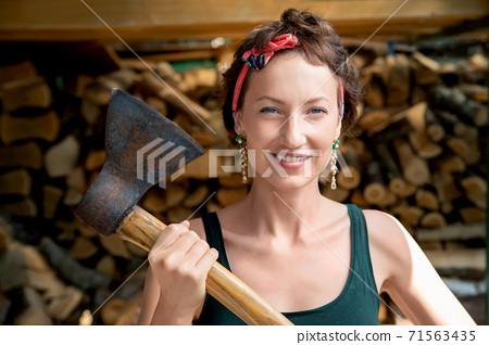 Young adult beautiful happy attractive caucasian brunette woman portrait have fun enjoy holding old rusty axe chopping firewood at wood store on backyard. Feminine women equality empowerment concept 71563435