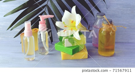 Soap, antiseptic spray and aromatic oil bottles, white lily flower on a wooden table, natural cosmetics, home body care products, healthy lifestyle, cleanliness 71567911