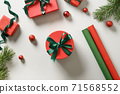 Wrapping Christmas gifts in red and green paper. 71568552