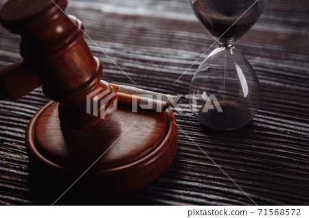 Judge gavel, hourglass and cigarette close-up. Tobacco law 71568572