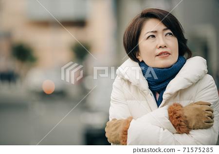 冬季婦女穿著羽絨大衣和寒冷的天氣 71575285