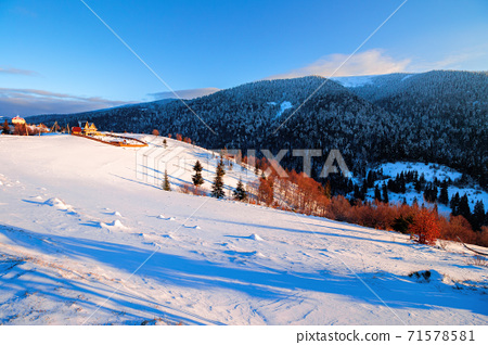 winter rural landscape at sunrise. trees and fields on snow covered hills. mountain ridge in the distance beneath a bright blue sky with clouds 71578581