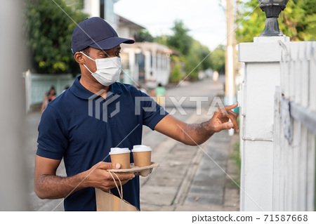 African American delivery Man with protective face mask ringing house doorbell at outdoor 71587668