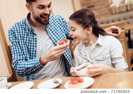 Father with Daughter Eating Cakes in Cafeteria. 71590804