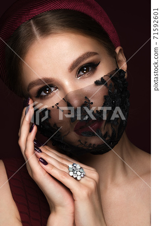 Portrait of a beautiful woman in a black lace mask and classic makeup. Mask mode during the covid pandemic 71592601